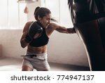female boxer hitting a huge... | Shutterstock . vector #774947137