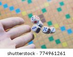 hand throwing white dice... | Shutterstock . vector #774961261