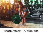 young woman lifting weights in... | Shutterstock . vector #775000585