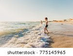 children on the beach go into... | Shutterstock . vector #775145965