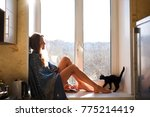 girl with a kitten at the window | Shutterstock . vector #775214419