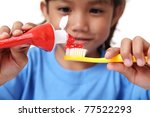 Young girl squeezing tooth paste on a toothbrush - stock photo