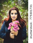 Small photo of A portrait of a goth redhead holding a bouquet of purple flowers