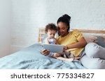 african woman holding tablet...   Shutterstock . vector #775334827