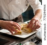 arranging focaccia on a plate | Shutterstock . vector #775394944
