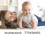 mom and baby boy playing in... | Shutterstock . vector #775436401