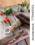 Small photo of several variety of traditional Corsican charcuterie on a wooden background with an olive branch and black olives abd arbitus bayberry