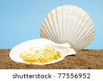 Omega three capsules in an opened seashell at the bottom of the ocean floor. - stock photo