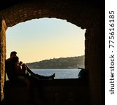 Small photo of Young couple in love enjoys the warm sunset light sitting hugging each other in front of the beauty of the Napoletan sea framed by an old stone arch at Castel dell'Ovo in Naples, Italy.