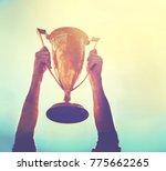 a man holding up a gold trophy... | Shutterstock . vector #775662265