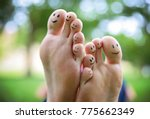 smiley faces on a pair of feet... | Shutterstock . vector #775662349