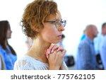 young woman praying in a church....   Shutterstock . vector #775762105