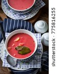Small photo of Vegetarian red soup - borsch in bowl on wooden background.
