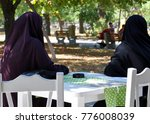 two Muslim women in a paranjas sitting at a table in a cafe in the park