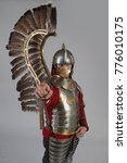 Small photo of Man in armor of hussar legion posing on gray background. Character for computer game.
