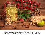 Small photo of mason jar with ice tea with ginger, lime, cinnamon and gingerbread, decorated Christmas tree branch, cones, red berries and anis, greeting card