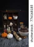 Small photo of Magical ingredients on rustic background woth artificial pumpkins. Workplace of a mage or witch