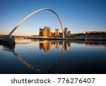 Millenium Bridge on Newcastle Quayside illuminated by the evening sun and reflected in the river Tyne
