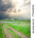 rural road in green grass under dramatic sky - stock photo