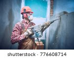 builder with hammer breaking wall indoors - stock photo