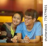Small photo of young man and young asian woman dating in cafe