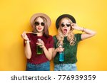 two hipster girls with drinks... | Shutterstock . vector #776939359