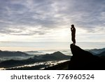 Man Praying On Cliff Against...