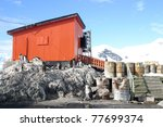 Adelie penguins in front of orange barrack and barrels with waste - stock photo