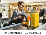 smiling female cashier scanning ... | Shutterstock . vector #777034621