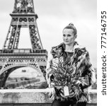 Small photo of The Party Season in Paris. modern fashion-monger with Christmas tree in fur coat in Paris, France looking into the distance