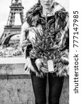 Small photo of The Party Season in Paris. Closeup on modern fashion-monger with Christmas tree in fur coat in the front of Eiffel tower in Paris, France
