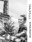 Small photo of The Party Season in Paris. Portrait of happy modern fashion-monger with Christmas tree in fur coat in Paris, France looking into the distance
