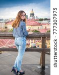 Small photo of leggy long-haired lass wearing blue jeans and blouse stands on the roof of the building in centre of Saint-Petersburg