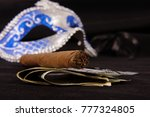 Small photo of Prostitution concept: luxury cigar, money, condoms and seduction domino mask