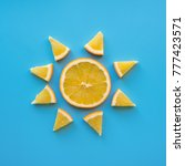 Small photo of Creative concept made from sliced orange like sun. Blue background. Sunny weather theme. Flat lay.