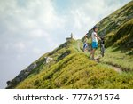 biker pushes bicycle up in the... | Shutterstock . vector #777621574