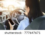 asian woman driving car with ... | Shutterstock . vector #777647671