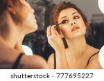 brunette woman applying make up ... | Shutterstock . vector #777695227
