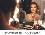 brunette woman applying make up ... | Shutterstock . vector #777695254
