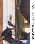 Small photo of Burglar tries on bright day with break pole break a door