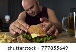 obese man cooking big burger ... | Shutterstock . vector #777855649
