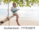an asian girl sits on a swing... | Shutterstock . vector #777910879