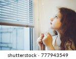 little kid on the window blinds ... | Shutterstock . vector #777943549
