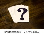 Small photo of Question mark on a wooden table