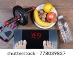 Small photo of Female feet on digital scales with word yes surrounded by sport accessories (AB roller wheel, fitness gloves), plate with healthy food and water bottle. Concept of active healthy lifestyle. Top view.