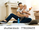 Small photo of Drawing attention. Cheerful emotional young father showing an interesting cartoon on the screen of a modern laptop while his cute little child smiling and holding a little bottle with tasty food