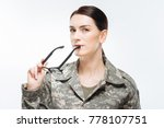 Small photo of Military obligation. Appealing positive intelligent woman carrying glasses while gazing straight and standing on the white background