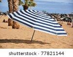Striped umbrella on the beach - stock photo