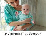 mother holding her child. young ... | Shutterstock . vector #778385077