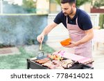 handsome man preparing barbecue ... | Shutterstock . vector #778414021
